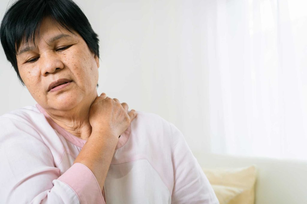 Woman holds neck in pain